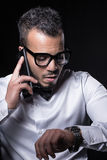 Studio portrait of young man. Portrait of man in white shirt talking by the phone and looking on the watch Royalty Free Stock Photos