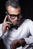 Studio portrait of young man. Portrait of man in white shirt talking by the phone and looking on the watch Stock Image