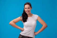 Studio portrait of a young beautiful woman in a white t-shirt against a blue wall background. People sincere emotions. Studio portrait of a young pretty woman stock photography