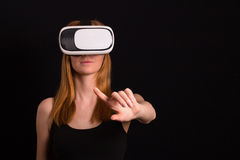Studio portrait of young redhead girl playing with virtual reali. Ty goggles for mobile game application Royalty Free Stock Photo