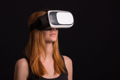Studio portrait of young redhead girl playing with virtual reali. Ty goggles for mobile game application Stock Images