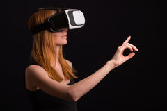 Studio portrait of young redhead girl playing with virtual reali. Ty goggles for mobile game application Stock Photography