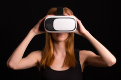 Studio portrait of young redhead girl playing with virtual reali. Ty goggles for mobile game application Royalty Free Stock Image