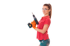 Studio portrait of young sexy brunette girl in uniform and glasses makes renavation with drill in hands smiling on. Camera isolated on white Royalty Free Stock Photos