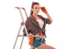 Studio portrait of young sexy brunette girl in uniform and glasses makes renavation on ladder and looking at the camera. Isolated on white Royalty Free Stock Image
