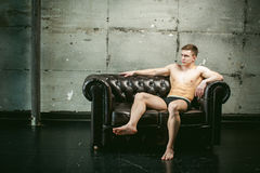 Studio portrait young sexy men bodybuilder athlete, with a bare torso. Young sexy man bodybuilder athlete sitting on a black leather couch with a naked torso Royalty Free Stock Photos