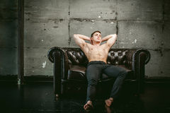 Studio portrait young sexy men bodybuilder athlete, with a bare torso. Young sexy man bodybuilder athlete sitting on a black leather couch with a naked torso and Royalty Free Stock Photo