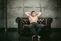 Studio portrait young sexy men bodybuilder athlete, with a bare torso. Young sexy man bodybuilder athlete sitting on a black leather couch with a naked torso and Stock Images