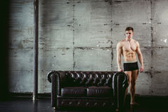Studio portrait young sexy men bodybuilder athlete, with a bare torso. Young sexy man bodybuilder athlete stands at black leather couch with a naked torso Stock Photos