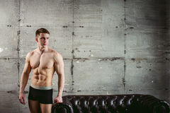 Studio portrait young sexy men bodybuilder athlete, with a bare torso. Young sexy man bodybuilder athlete stands at black leather couch with a naked torso Royalty Free Stock Photography