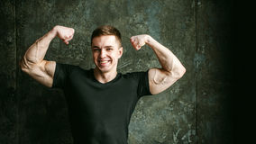 Studio portrait young sexy men bodybuilder athlete. Young sexy man bodybuilder athlete, studio portrait loft on background of stylized Concrete brutal wall, guy Royalty Free Stock Image