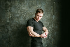 Studio portrait young sexy men bodybuilder athlete. Young sexy man bodybuilder athlete, studio portrait loft on background of stylized Concrete brutal wall, guy Royalty Free Stock Photography