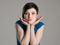 Studio portrait of young short hair beauty resting head on her open hands Stock Photography