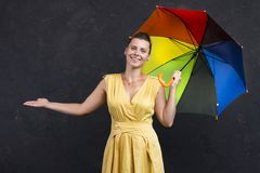 Studio portrait of young woman in a dress with an umbrella in her hand. Weather forecast Stock Image