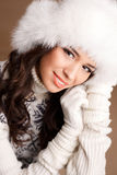 Studio portrait of a young woman in fluffy white hat and mittens Stock Images