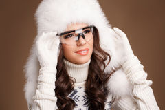 Studio portrait of a young woman in fluffy white hat and mittens Stock Image
