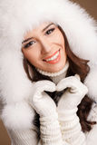 Studio portrait of a young woman in fluffy white hat and mittens Royalty Free Stock Photo