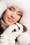 Studio portrait of a young woman in fluffy white hat and mittens Royalty Free Stock Photography