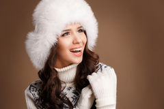 Studio portrait of a young woman in fluffy white hat and mittens Royalty Free Stock Images