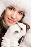 Studio portrait of a young woman in fluffy white hat and mittens Stock Photo