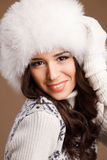 Studio portrait of a young woman in fluffy white hat and mittens Stock Photos
