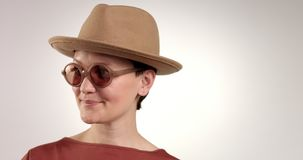 Studio portrait of young woman in hat smiling and watching at camera. In sunglasses stock video footage