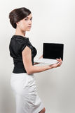 Studio portrait of young woman holding laptop. Studio portrait of young woman dressed in a black and white suit holding laptop stock photo