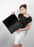 Studio portrait of young woman with laptop. Studio portrait of young woman in black and white suit with laptop stock image