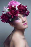 Studio portrait of young woman with peony in head. Portrait of young woman with peony in head royalty free stock images