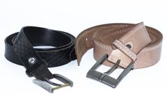 Old, used men`s brown and black leather belt with patina set on a plain white background. royalty free stock photography