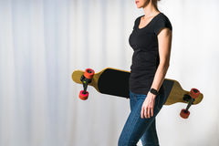 Studio. In the right part of the image is a young woman in a black T-shirt and jeans standing and holding a longboard. Royalty Free Stock Images