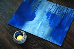 Blue painting brush and candle in candlestick. Studio scenes, the picture in the process, the cozy atmosphere of the Studio Royalty Free Stock Images
