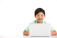 Studio schoss vom chinesischen Jungen mit Laptop Lizenzfreie Stockbilder