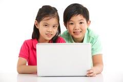 Studio schoss von zwei chinesischen Kindern mit Laptop Lizenzfreies Stockbild