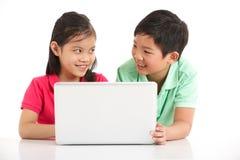 Studio schoss von zwei chinesischen Kindern mit Laptop Lizenzfreie Stockfotografie