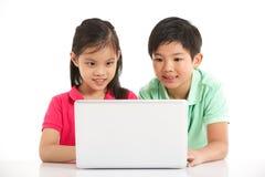 Studio schoss von zwei chinesischen Kindern mit Laptop Stockbild