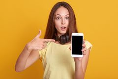 Free Studio Sho Of Adorable Woman Showing Phone With Blank Screen And Pointing On It With Her Index Finger, Has Astonished Facial Royalty Free Stock Photo - 155678885