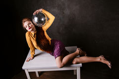 Studio shoot of posing woman holding disco ball.  Retro style. Royalty Free Stock Image