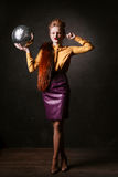 Studio shoot of posing woman holding disco ball.  Retro style. Royalty Free Stock Images