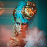 Studio shoot of woman with creative hairstyle, makeup and dress. Studio shoot of young woman with creative hairstyle, makeup and dress. Exotic bird royalty free stock images