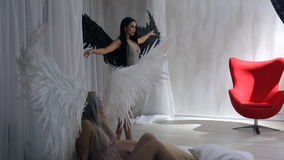 Studio shooting of two models blond and brunette angels with wings. An attractive black haired model with earth tone makeup in the background puts arms in a stock video
