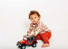 Studio shot of adorable african 1 year old baby boy playing with ccar royalty free stock image
