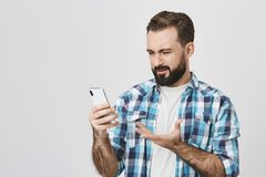 Studio shot of adult bearded brunette male employer, holding gadget in hand and gesturing with perplexed and. Disappointed expression, standing over gray Stock Image