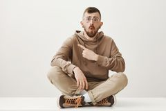 Studio shot of amazed pleased young european male student in glasses and stylish outfit sitting with crossed legs on. Floor and pointing left with forefinger Royalty Free Stock Image