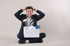 Studio shot of angry businessman with office stuff in the box si Royalty Free Stock Images