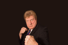 Studio shot of angry senior businessman with fist raise against dark background Royalty Free Stock Photo
