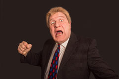 Studio shot of angry senior businessman with fist raise against dark background Royalty Free Stock Images
