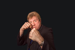Studio shot of angry senior businessman with fist raise against dark background Stock Photos