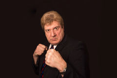 Studio shot of angry senior businessman with fist raise against dark background. Studio shot of angry senior businessman with fist raised against black Royalty Free Stock Photo