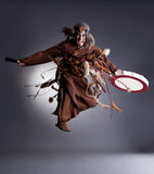 Studio shot of angry shaman posing in jump. On gray background Stock Photos